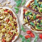 Foto av to pizzaer på bakepapir. Det er en pizza nederst til venstre med cashewost på i form av gule, tykk saus-aktige striper. Det er også knuste tortilachips og tomatbiter på den. Pizzaen til høyre har lignende fyll, men ikke knust tortillachips. Den har istedet ruccolablader på seg.