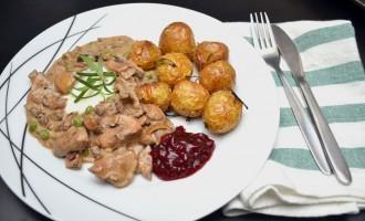 Foto av en asjett med soppgryte på venstre side og ovnsbakte, hele, små poteter med skall på på høyre side. Nederst til høyre på asjetten er en spiseskje tyttebærsyltetøy. Oppå soppgryten på venstre siden er en klæsj vegansk rømme, pyntet med flere stilker frisk rosmarin. På høyre side er det en brettet stoffserviett med blå og hvite horisontale striper og gaffel og kniv i enkel stålutforming oppå.