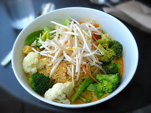 Foto av hvit, dyp skål med forskjellige grønnsaker som blomkål, brokkoli iog minimais i en rød currysaus.