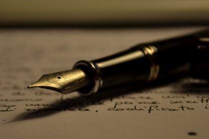 Mørkt bilde av en gammeldags fyllepenn som ligger på et ark som det er skrevet utydelig tekst på.
