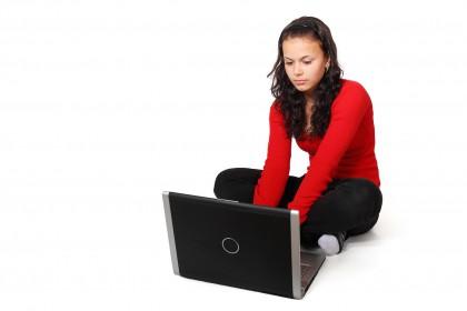 Ung kvinne med rød genser og svart bukse sitter på gulvet med bena i kryss, med en svart bærbar datamaskin foran seg, som hun ser på, og ser ut som hun skriver.