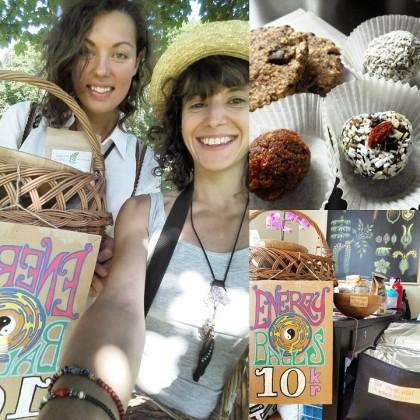 """Fotografi av to jenter (selfie) på t-banen. De smiler og holder opp to kurver foran seg, den ene med teksten """"Energy balls"""" i sirlig skrift på en plakat festet på kruven, og med yin og yang-symbolet malt på. Det er goså foto av rå, vegansk snacks – runde baller med nøttestrøssel i muffinsformer og rå cookies."""