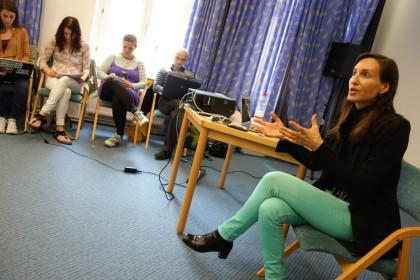 Skrått bilde av Melanie Joy iført turkis bukse og svart jakke. Hun sitter på en stol med beina i kryss, prater og gestikulerer med hendene. Fire deltagere på motsatt vegg ses; de sitter foran vinduer og gardiner.
