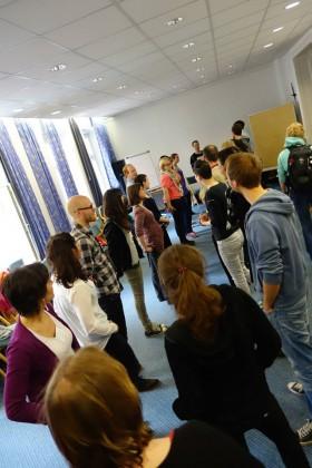 Oversiktsbilde av et rom med ca 20 mennesker spredt utover gulvet. De står omtrent på to rekker, men bildet er skrått og får det til å se litt tilfeldig ut.