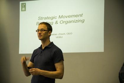 """Sebastian Zösch foran en vegg med et skjermbilde fra en powerpoint på veggen. Sebastian har på seg en blå t-skjorte og briller. Han gestikulerer med hendene. Teksten på """"skjermen"""" er """"Strategic Movement Building & Organizing""""."""