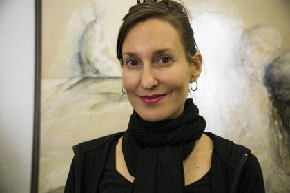 Portrettbilde av Melanie Joy. Hun har brunt, oppsatt hår, smiler, og er ikledd svart genser og svart sjal.