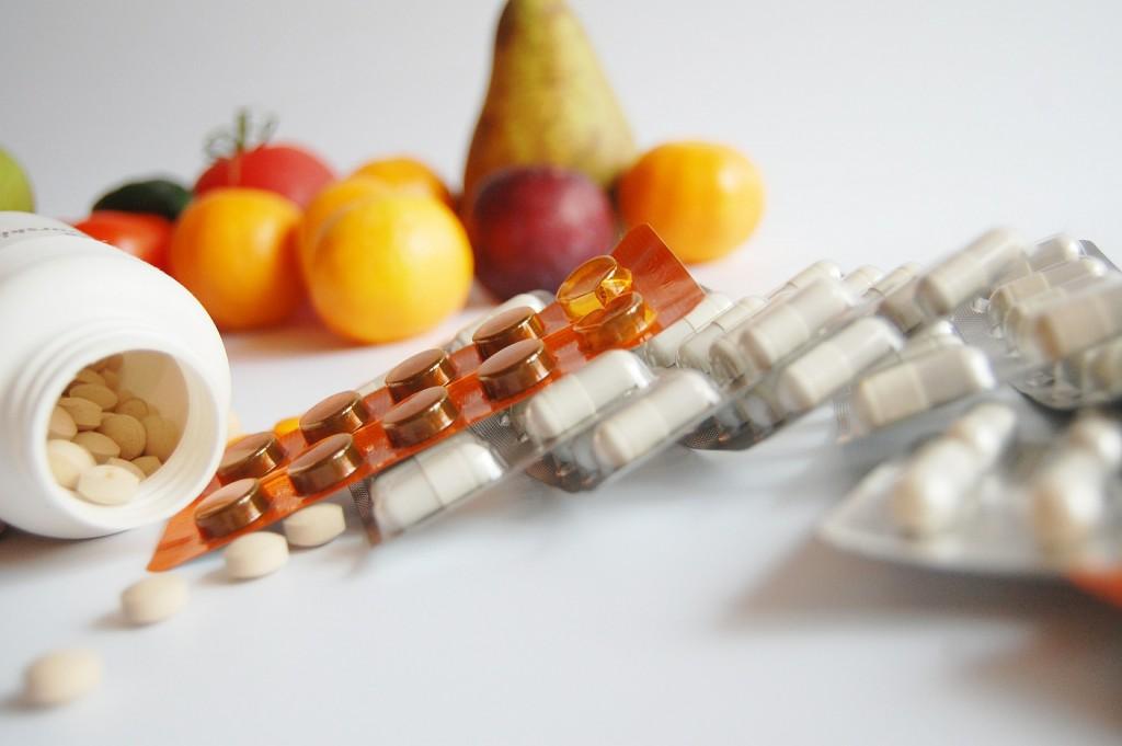 Fotografi av tre aluminiumsbrett med legemidler i forgrunnen, samt en åpnet legemiddelboks liggende på siden med tabletter inni. I bakgrunnen ser vi gule og lilla plommer og en pære stilt opp. Alt ligger/står på hvit bakgrunn.