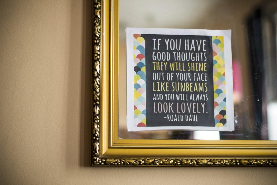 """Bilde av et hjørne av et speil, med et ark på, med sitat fra Roald Dahl: """"If you have good thoughts, they will shine out of you like sunbeams, and you will always look lovely."""" Hvit tekst på svart bakgrunn, med hvit ramme og farget sirkelmønster rundt. Speilet har gullramme."""
