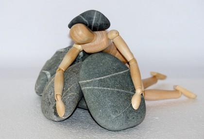 Et bilde av en anatomisk tredukke som ligger oppå steiner, vent nedover, med en stein oppå ryggen.