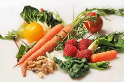 Foto av gulrøtter, valnøtter, grønn salat, bringebær, gul tomat og drue liggende på en hvi bakgrunn. Bildet er tatt litt skrått ovenfra, og er ganske tett på. Bildet er lyst og fullt av friske farger.