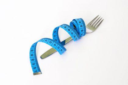 En gaffel med blått målebånd surret rundt, hvit bakgrunn.