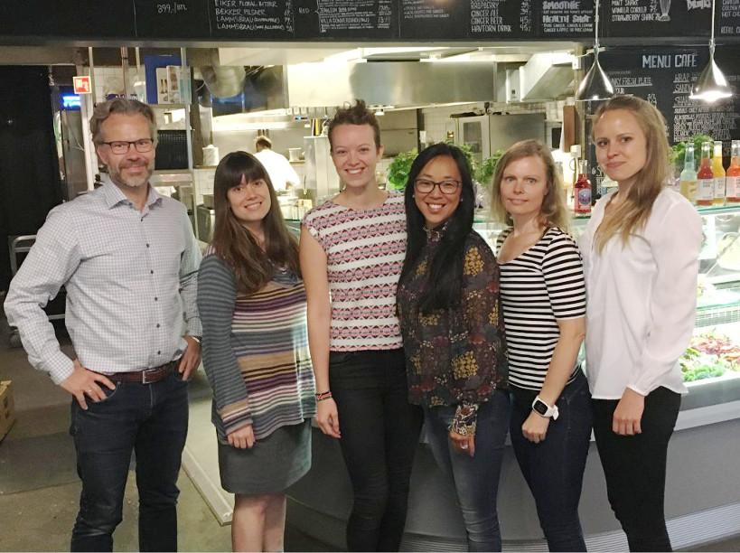 Fotografi av seks personer (en mannlig-represerened og fem kvinnelig-presenterende) som står oppreist og ser rett inn i kameraet og smiler.