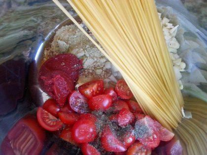 Nærbilde av tørr spaghetti, tomater og krydder i kaserolle.