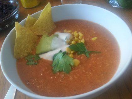 Hvit bolle med rødfarget suppe med tre tortillachips, litt rømme, litt mais og frisk koriander på toppen.