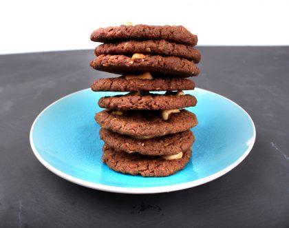 Blå tallerken med en høy stabel av brune cookies, på svart underlag og en hvit vegg i bakgrunnen