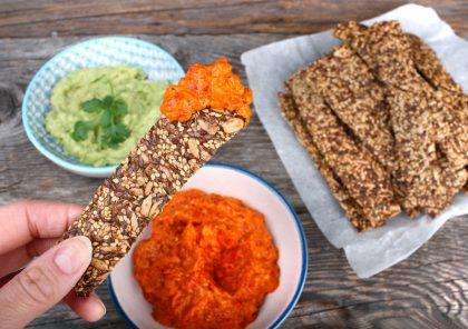 I forgrunnen holder en hånd en knekkebrød-pinne som er blitt dyppet i rød dip, i bakgrunnen er et treunderlag med en skål med guacamole, en skål med rød dip og en haug med knekkebrødpinner