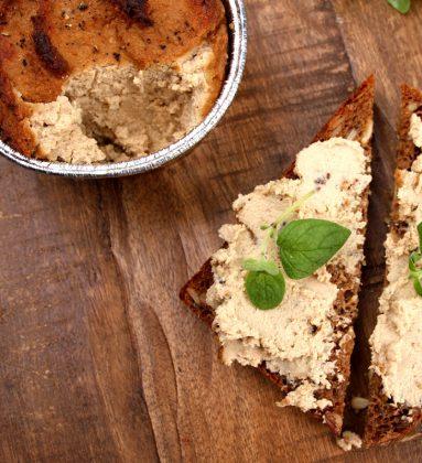 En skål med leverpostei og en brødskive oppdelt på skrå dekket med leverpostei og grønne urter, på underlag av tre