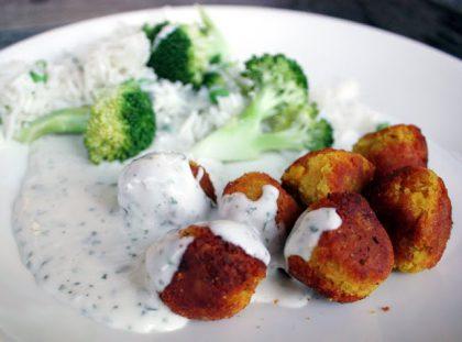 Hvit tallerken med runde middagskaker, brokkoli og hvit saus