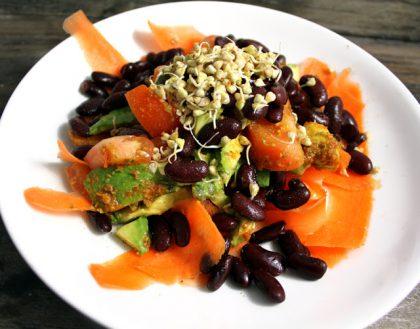 Hvit tallerken med salat på, bestående av blant annet gulrot, avokado og bønner.