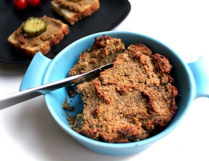 Foto av en blå, dyp skål fykt med ovsnbakt linsepostei med en kniv på skrå nedi. I bakgrunnen ser vi to brødskiver med linsepostei og sylteagurk på en sort, firkantet tallerken.