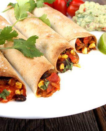 Fire tortillalefseruller med fyll, toppet med frisk koriander. Man kan skimte guacamole og småtomater i bakgrunnen. Hvit tallerken.