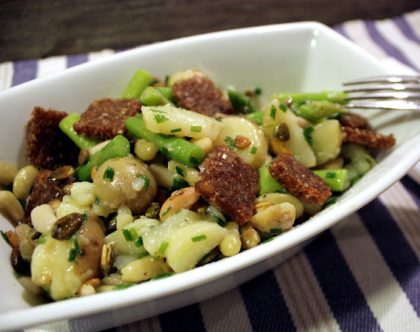 Avlang og dyp tallerken med poteter, krutonger og bønner i.