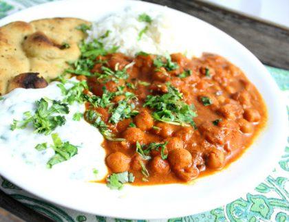 Hvit tallerken med rødfarget gryterett med kikerter, naan-brød, ris og vegansk rømmedressing, toppet med friske urter