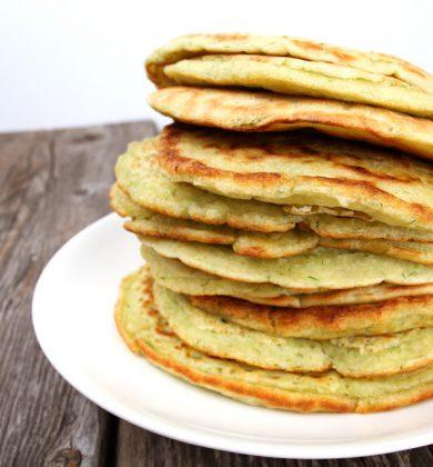 En høy stabel med pannekaker med såvidt grønnskjær, oppå hvit tallerken som står på treunderlag