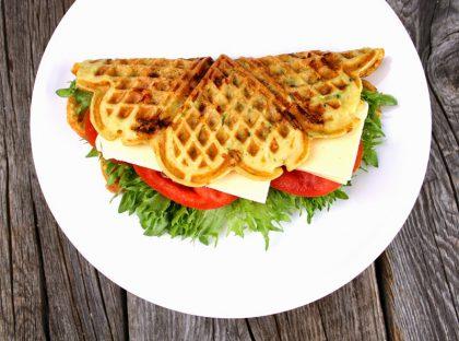 Hvit tallerken med en brettet vaffel på, med salat, paprika og ost inni.