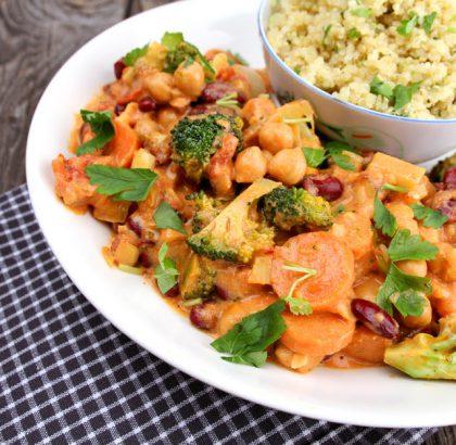 Nærbilde av hvit tallerken med oransjefarget gryterett hvor man ser brokkoli, kikerter og gulrotbiter med mer, og i bakgrunnen på tallerkenen står en skål med bulgur