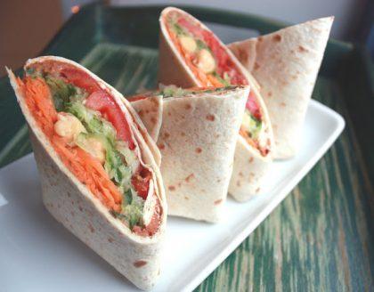 Hvit, firkantet tallerken med fire halve wraps på, med revet gulrot, hummus, tomat og avokado inni.